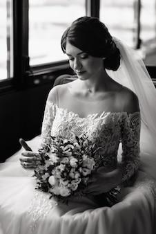 Счастливая невеста сидит возле окна и посмотреть на свадебный букет. красивая молодая женщина в белом платье с букетом цветов.