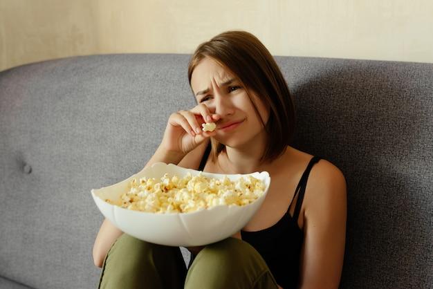 Эмоциональная милая девушка плачет во время просмотра драмы, ест попкорн, дома.