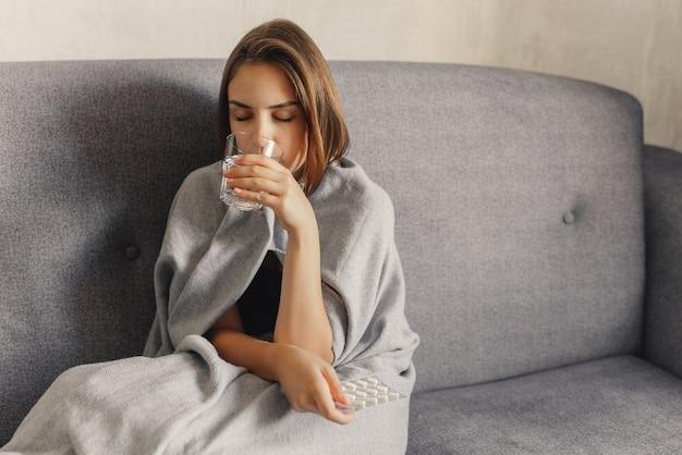 Женщина, завернутая в серое одеяло, держит таблетки и питьевую воду, замерзает, сидит на диване, дома.
