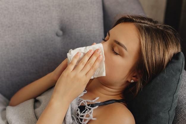 病気の女性、ハンカチを持って、くしゃみをして、凍りついて、自宅のベッドに横たわって