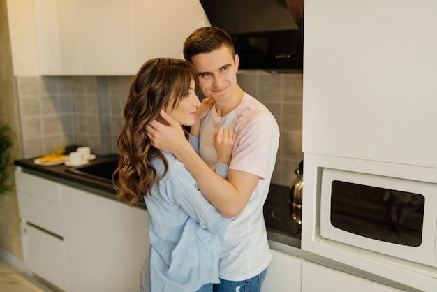 一緒に楽しい時間を過ごすキッチンで若いカップルの笑顔。関係の概念。