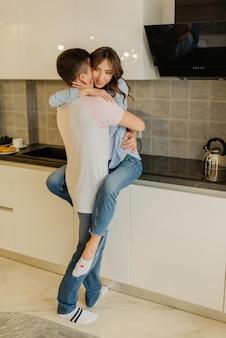 Красивая молодая пара, проводить время вместе в кухне дома. девушка в любви и ее парень обнимаются. влюбленная пара концепции.
