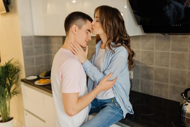 若い男は彼の女の子を抱擁し、女の子は男の額にキスします。一緒に楽しい時間を過ごすキッチンで若いカップルを愛する。関係の概念。