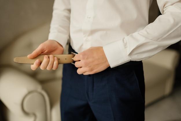 青いズボンと白いシャツの新郎が彼の革のベルトを締めます。朝の新郎。結婚式の詳細。コンセプトと構成。ビジネスマンの男性とビジネス。
