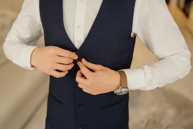 新郎は新郎の朝の集まりで彼のベストにボタンを留めます。新郎の結婚式の準備。