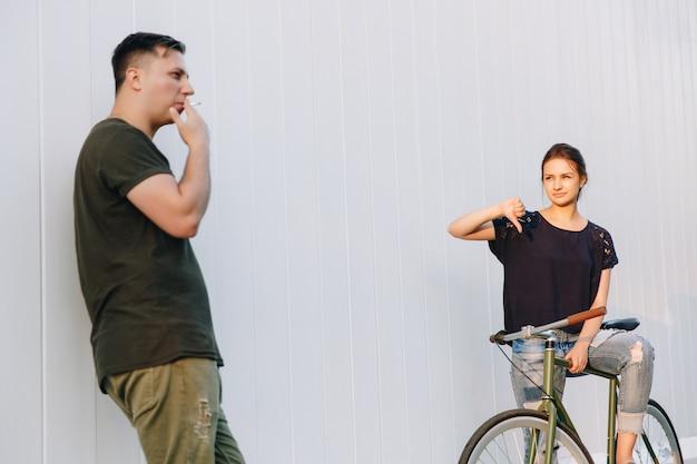 ファッショナブルな魅力的な男が中指を見せ、自転車でかわいいプリティウーマンに性交サインをしている間、彼女は彼のジェスチャーで親指を下に見せています。屋外。