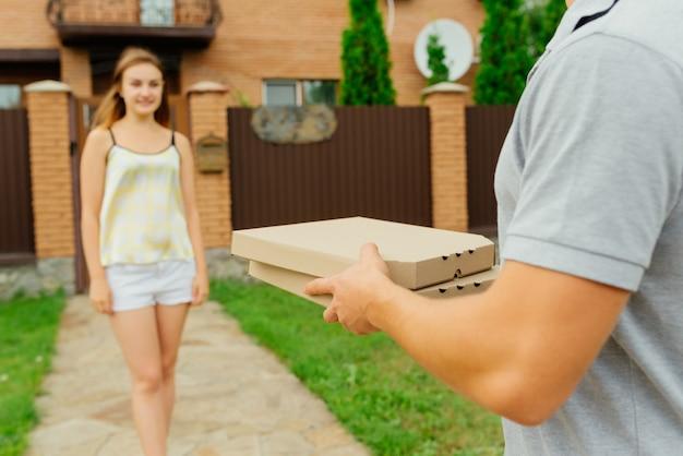 可愛らしい可愛い女性の野外写真は、民家の近くにあるピザを手に入れる為に配達員に向かいます。