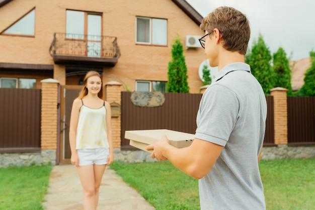 若い女性は個人宅で宅配便からピザを取得する予定です