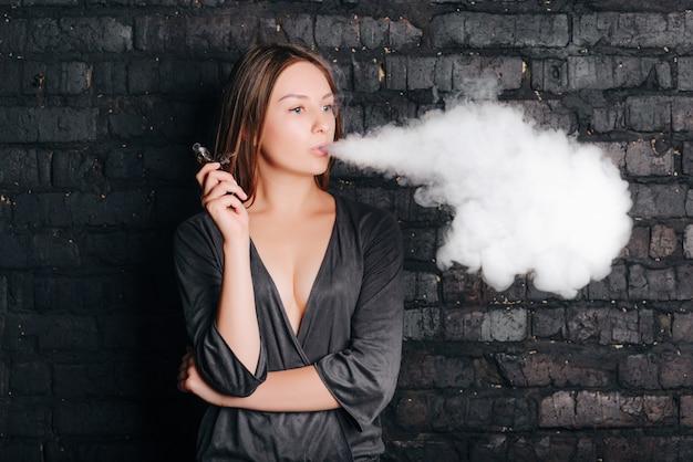 大きな煙の雲を吐きながら、タバコのないタバコを吸うトレンディな美しい少女。流行の服を着ています。