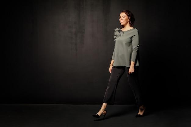 Успешная деловая женщина в серой блузке выходит вперед
