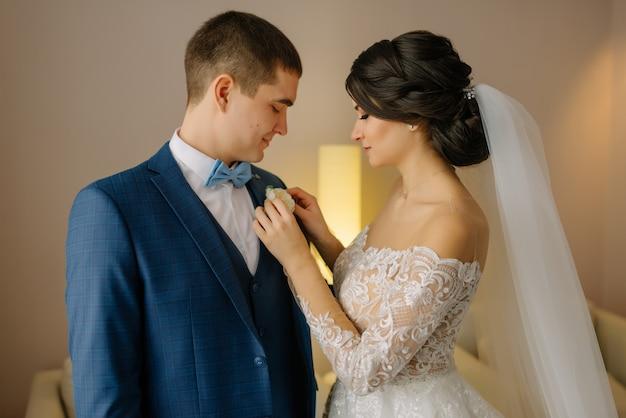 結婚式の朝の準備、新郎はボタンホールに置かれます。花嫁は新郎のブートニアを着ています。結婚式のための朝の準備新婚夫婦。結婚式のアクセサリー。