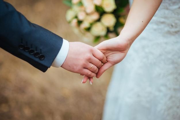 Руки влюбленных молодоженов с кольцами
