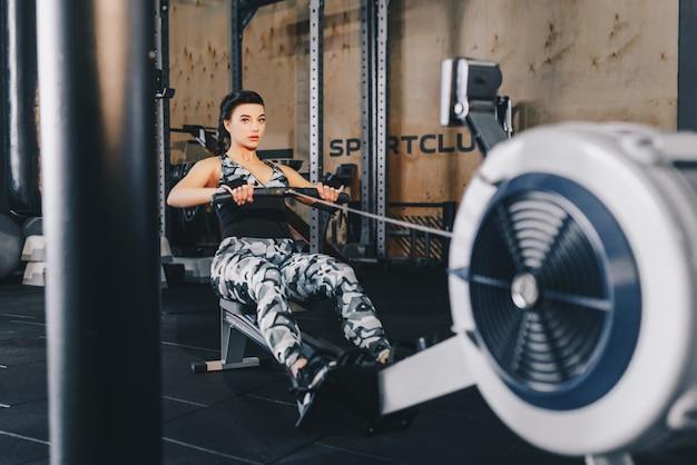 ジムのローマシンでワークアウトの女性に合います。トレーニング女性クロストレーニングフィットネスジムでローイングマシンを使用して有酸素運動。