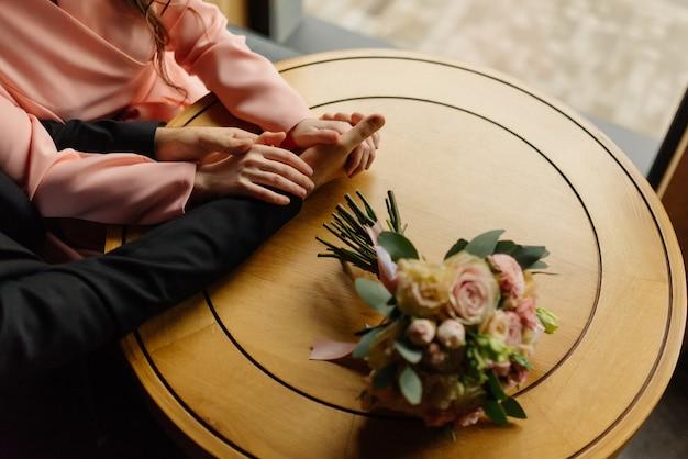 新郎は花嫁を手で持っています。閉じる。愛する新郎新婦がカフェに座っています。愛、ウェディングブーケ。幸せな新婚カップル。結婚式の詳細。上面図。