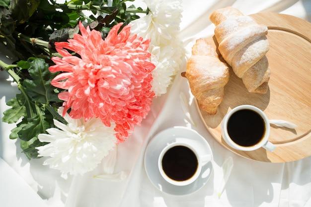 Два черных кофе и круассаны на белой кровати. концепция завтрака
