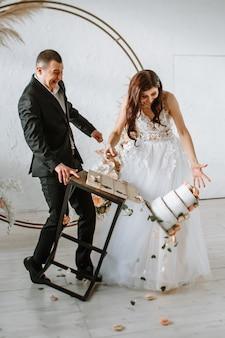Трехъярусный свадебный торт падает со стола. эмоции жениха и невесты, когда выпадает торт