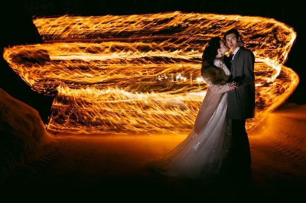 Жених обнимает невесту на фоне пламени, стоящего на снегу. техника ночной фотосъемки путем замораживания света и освещения.