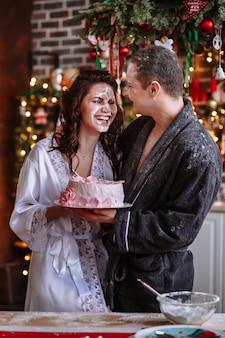 Парень положил голову девушки в торт, и они его размазали. действие происходит на кухне, украшенной к празднованию рождества и нового года
