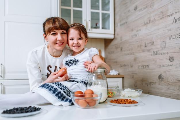 小さな女の子が台所のテーブルに座って、笑みを浮かべて、母親が彼女の隣に立っています。
