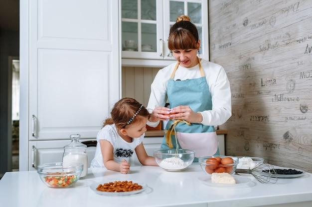 小さな女の子は母親が卵を粉の容器に割る