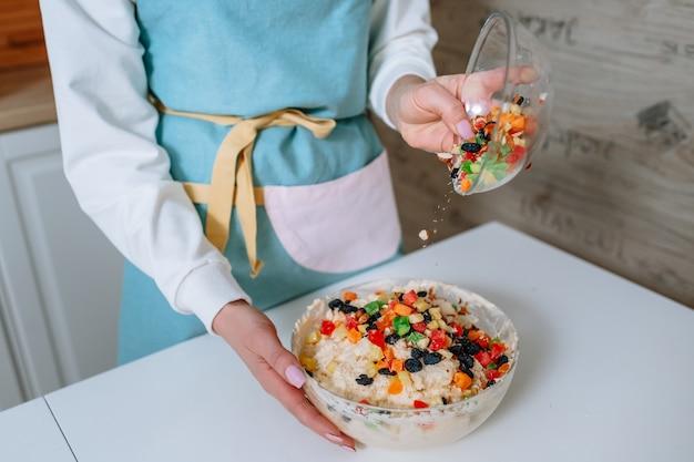 Женщина-повар добавляет в тесто цукаты. процесс смешивания ингредиентов торта на домашней кухне