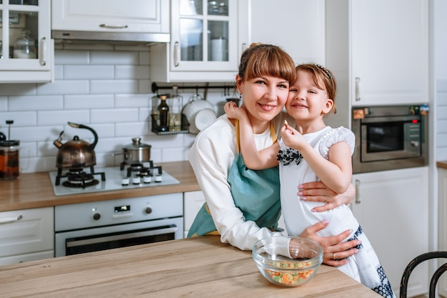 笑顔の女性が母親を抱擁します。台所の人々