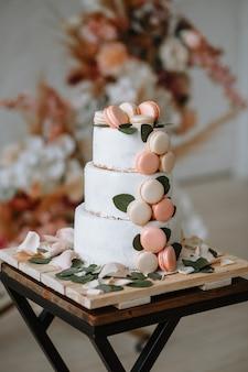 Трехъярусный свадебный торт на подставке на фоне арки