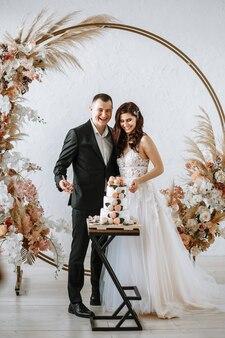 Молодожены собираются разрезать трехуровневый свадебный торт