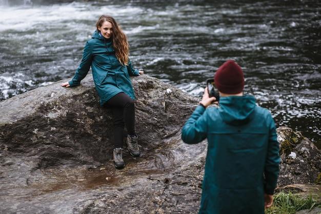 Парень фотографирует свою подругу на телефон на фоне водопада