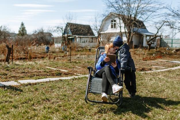 椅子に座っている女性が息子にタブレットで何かを見せています。古いれんが造りの家ダーチャを背景にすべてが起こります