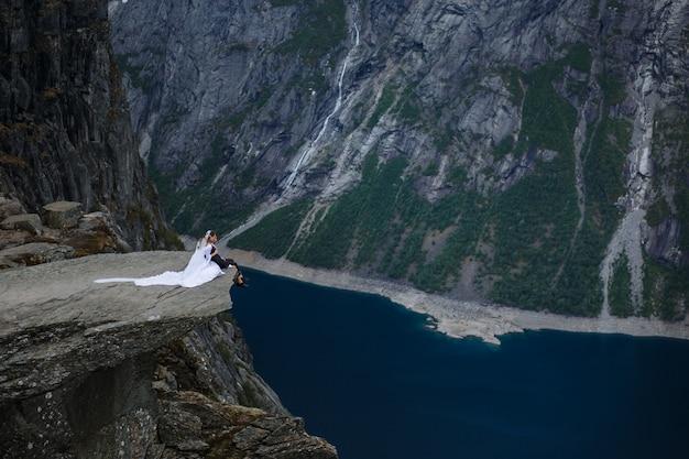フィヨルドを背景に、山の岩の断片の上に座って新郎新婦