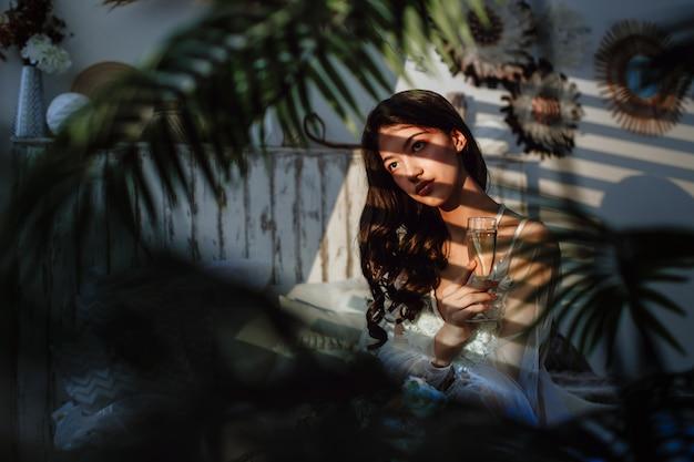 Азиатская невеста на кровати с бокалом шампанского в руке. размышления на лице