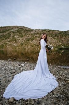 湖の岸に立っている長いウェディングドレスの花嫁