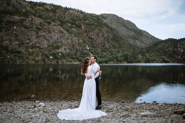 湖の岸に腕を組んで立っている結婚式のカップル