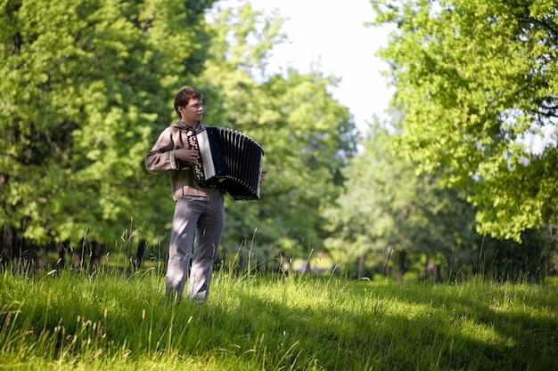 Мужчина в традиционной славянской одежде играет на баяне посреди леса