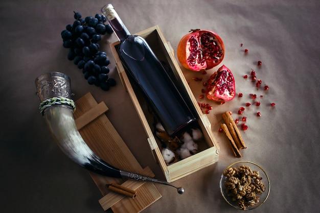 Бутылка красного виноградного вина в деревянной коробке. рядом находятся гранаты, черный виноград и рог для питья.