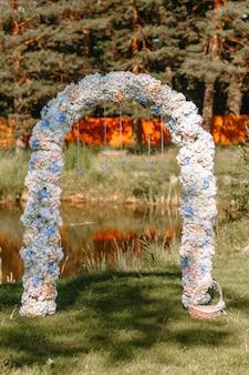 芝生の上に立って、写真撮影のための装飾的な結婚式のアーチ