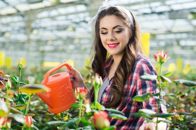 Счастливая молодая женщина заливки цветов в теплице