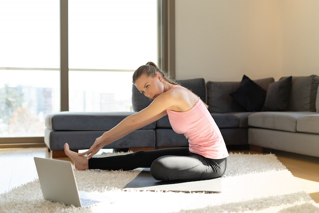 Интернет фитнес. молодая женщина делает упражнения на коврик для йоги напротив ноутбука