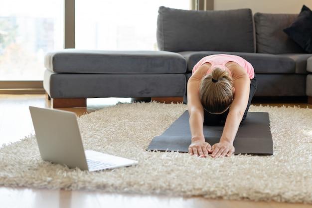 Онлайн фитнес занятия йогой. молодая женщина напротив ноутбука