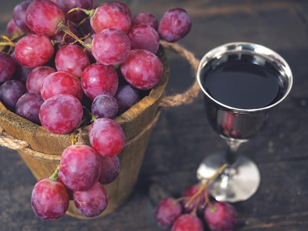 Красное вино и виноград. вино и виноград в старинных условиях с пробками на деревянный стол
