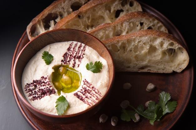 Хумус с хлебом на глиняной тарелке