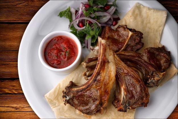 Жареные ребрышки на белой тарелке с соусом и луком. на деревянной доске