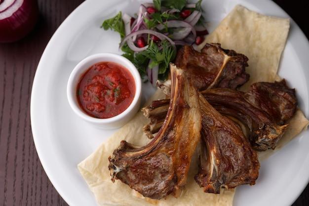 Жареные ребрышки на белой тарелке с соусом и луком