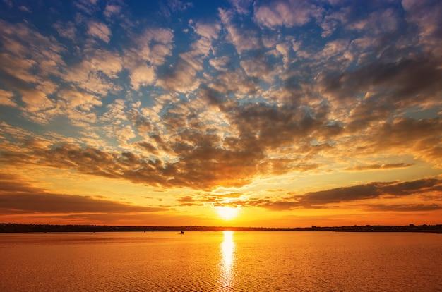 雲と水の反射で湖に沈む夕日