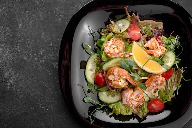 黒の背景に、エビの野菜サラダ