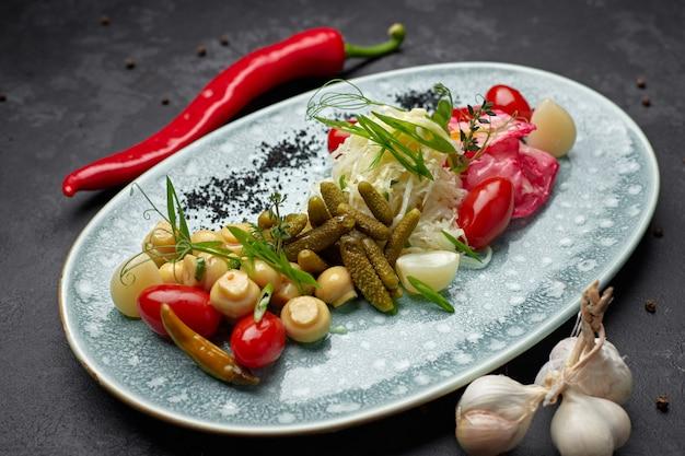 Маринованные овощи с грибами на темном фоне