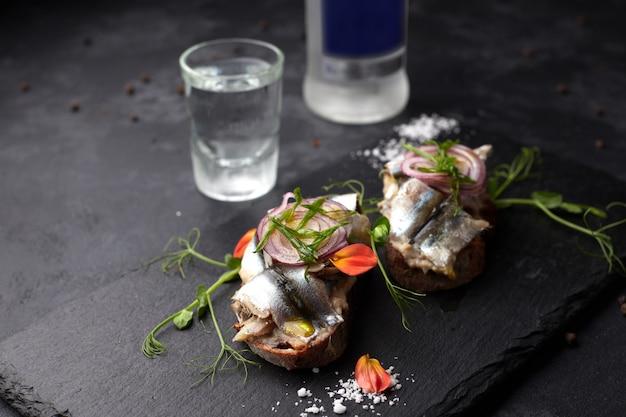Бутерброды с рыбой тюль на черном фоне. брускетты, водка, стекло, бутылка