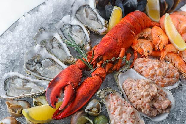 Красный лобстер на льду, с морскими гребешками, креветками и мидиями