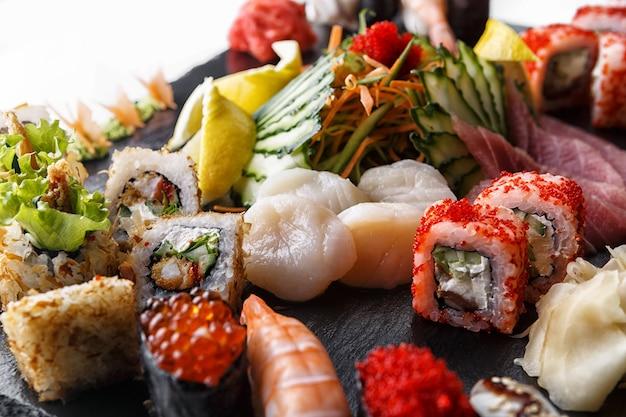 Суши набор роллов с морскими гребешками и овощами, на черном камне